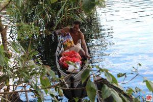 Salah satu kepala keluarga membawa barang bantuan dengan sampannya (Foto: Caritas Palangkaraya).